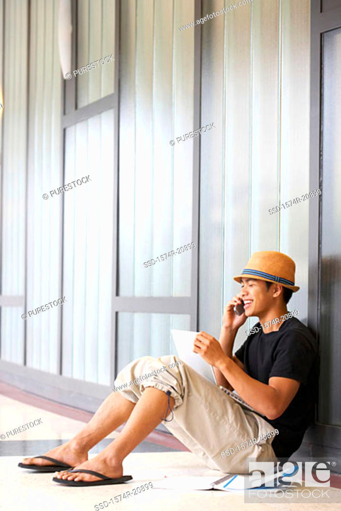Stock Photo: Side profile of a college student sitting in a corridor and talking on a mobile phone.