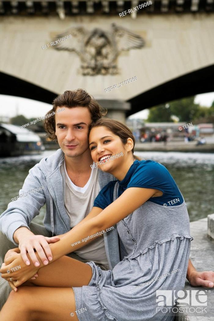 Stock Photo: Young couple embracing on steps by river Seine, Paris, France.