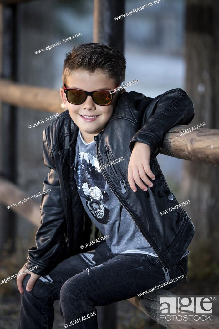 Stock Photo: Stylish little boy in sunglasses and brutal outfit posing with confidence at camera.