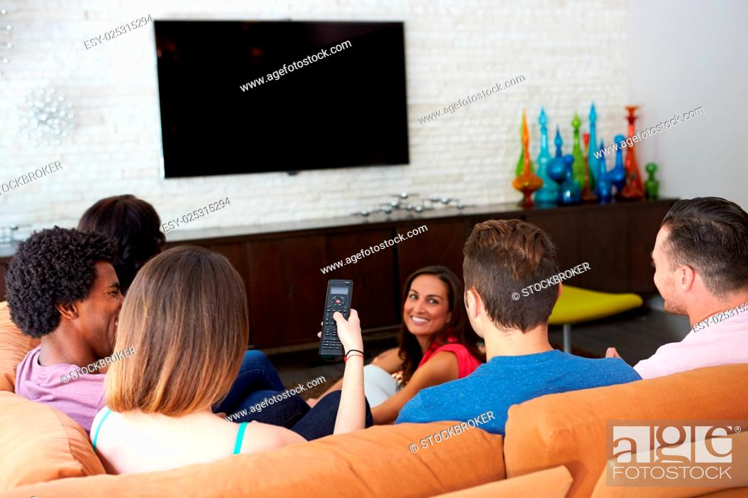 Stock Photo: Group Of Friends Sitting On Sofa Watching TV Together.