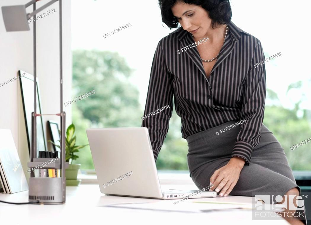 Stock Photo: Businesswoman sitting on table and using laptop.