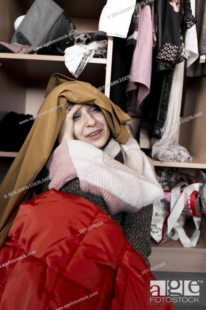 Stock Photo: young woman overwhelmed by her clothes, in front of wardrobe.