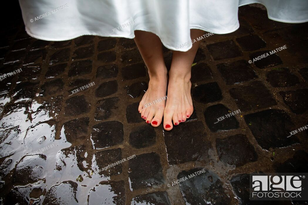 Imagen: Bride's bare feet on wet san pietrini stones in Rome Italy.