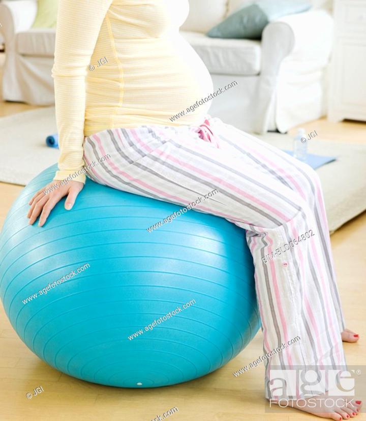 Stock Photo: Pregnant Asian woman sitting on exercise ball.