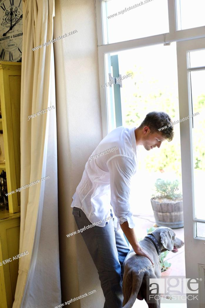 Stock Photo: Side profile of a man standing at door with dog.