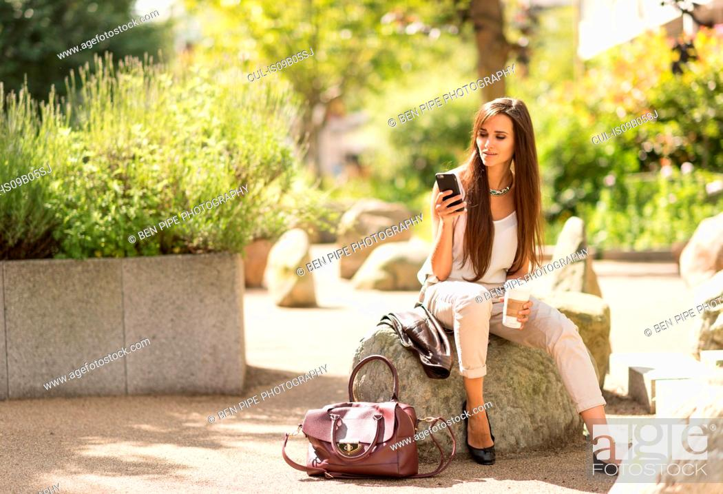 Stock Photo: Young businesswoman reading smartphone text in city park.