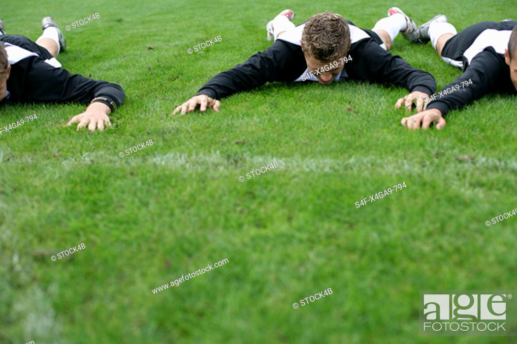 Stock Photo: Soccer player lying on his stomach on grass.