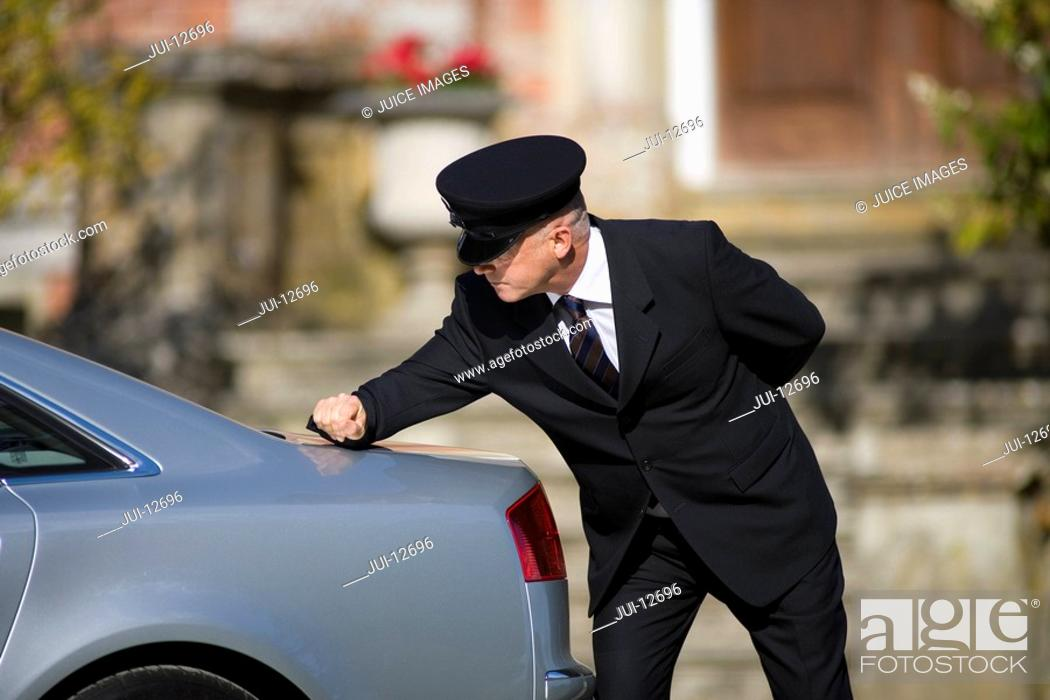 Stock Photo: Chauffeur polishing back of car outdoors.