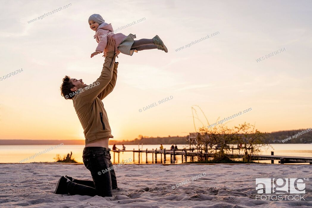 Imagen: Germany, Bavaria, Herrsching, father and daughter playing on the beach at sunset.