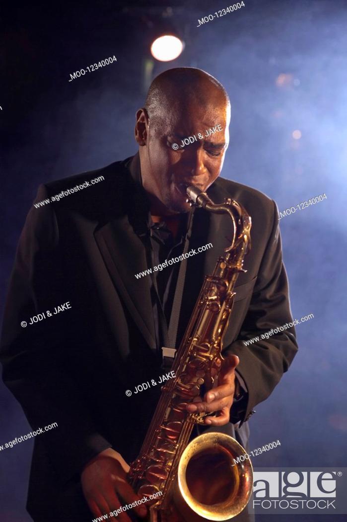 Stock Photo: Jazz musician playing saxophone on smokey nightclub stage.