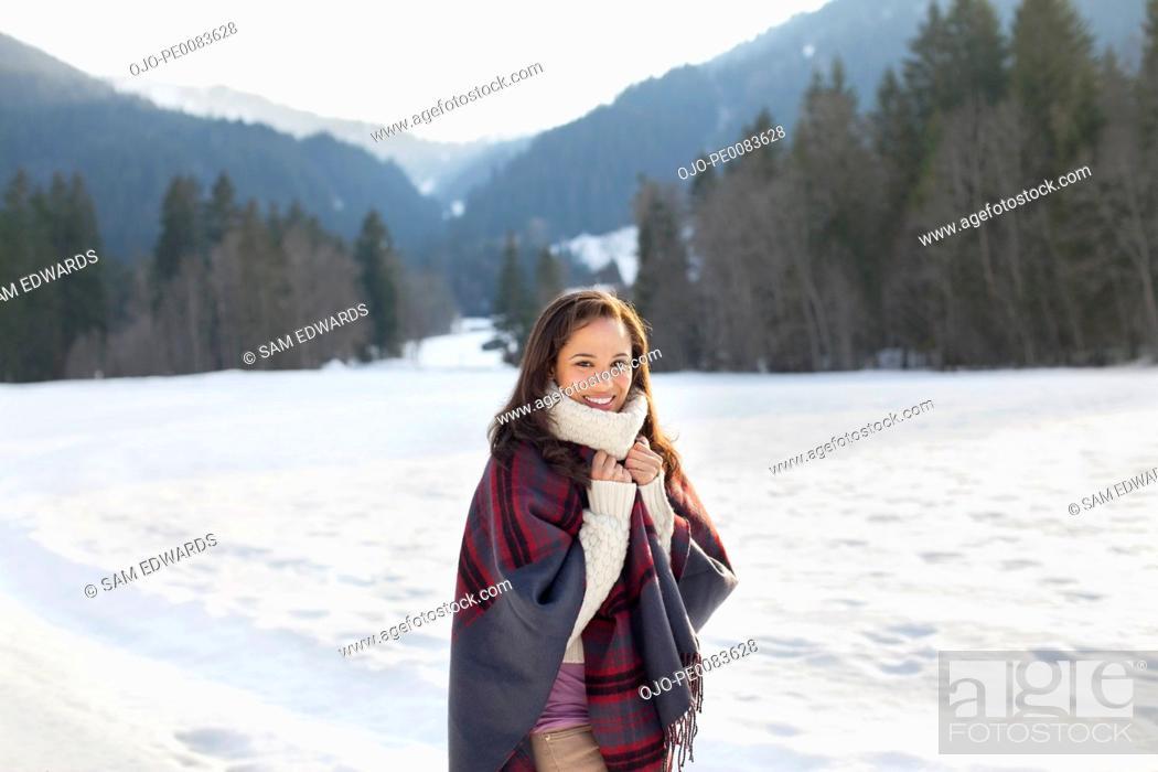 Stock Photo: Portrait of smiling woman in snowy field.