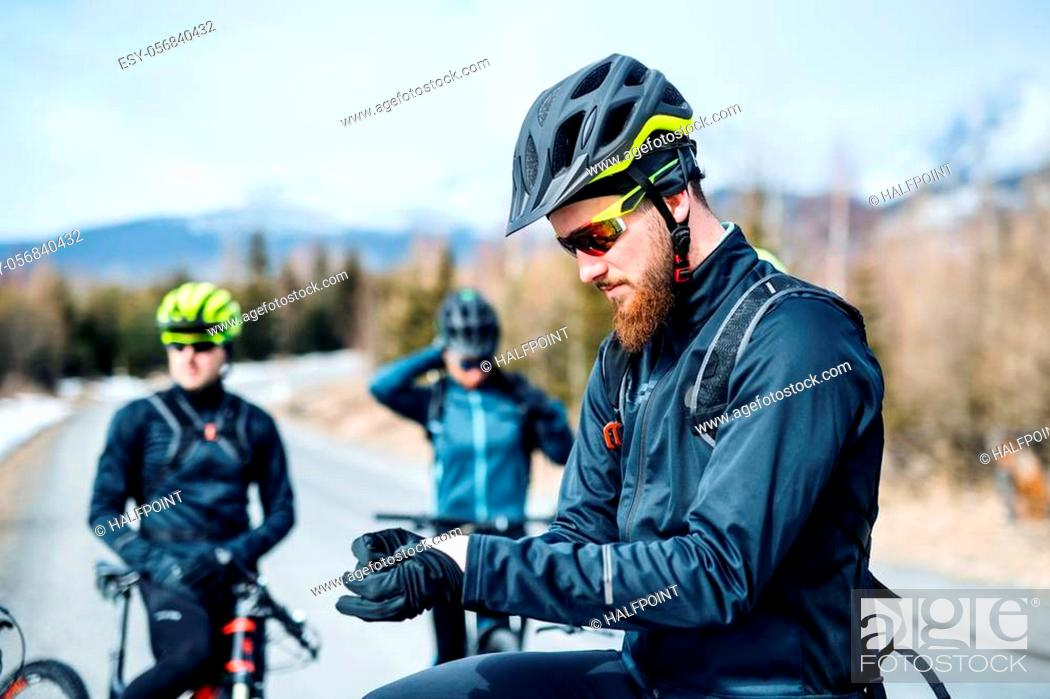 Imagen: A group of young mountain bikers standing on road outdoors in winter.