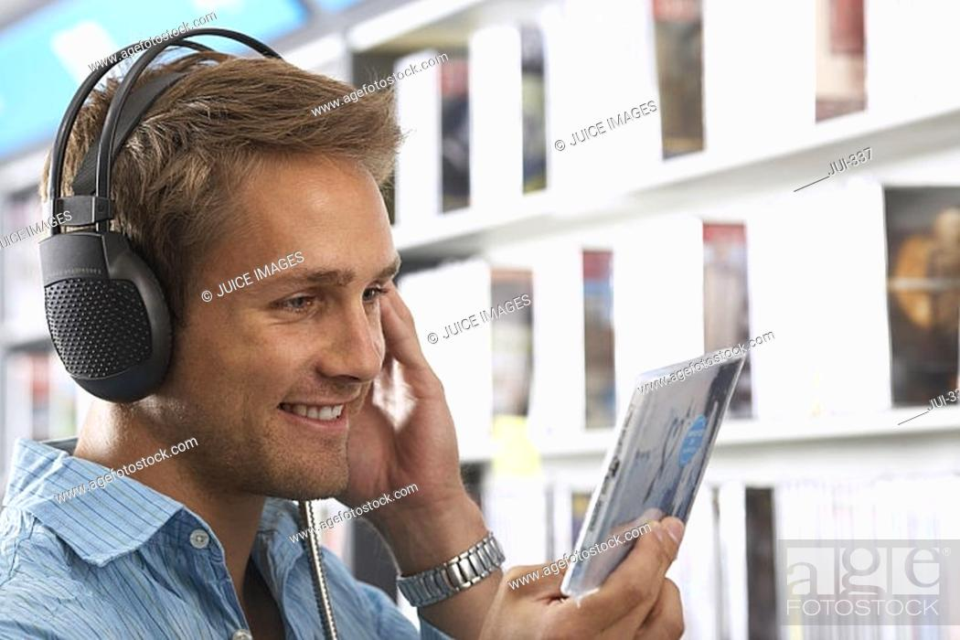 Stock Photo: Young man wearing headphones, listening to CDs in record shop, smiling, close-up, side view.