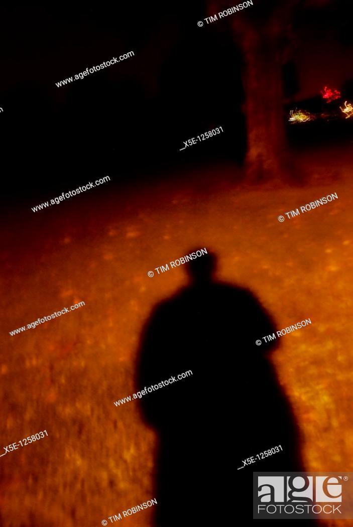 Stock Photo: Sinister shadow of figure under streetlight.