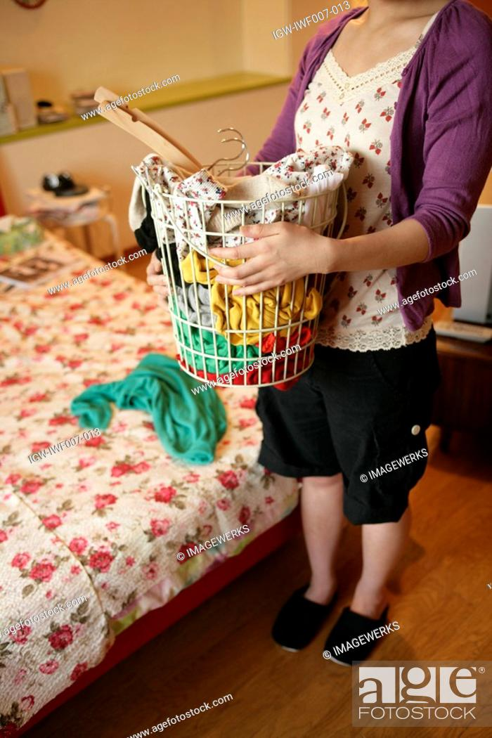 Stock Photo: A young woman holds a basket full of clothes as she stands near the bed.