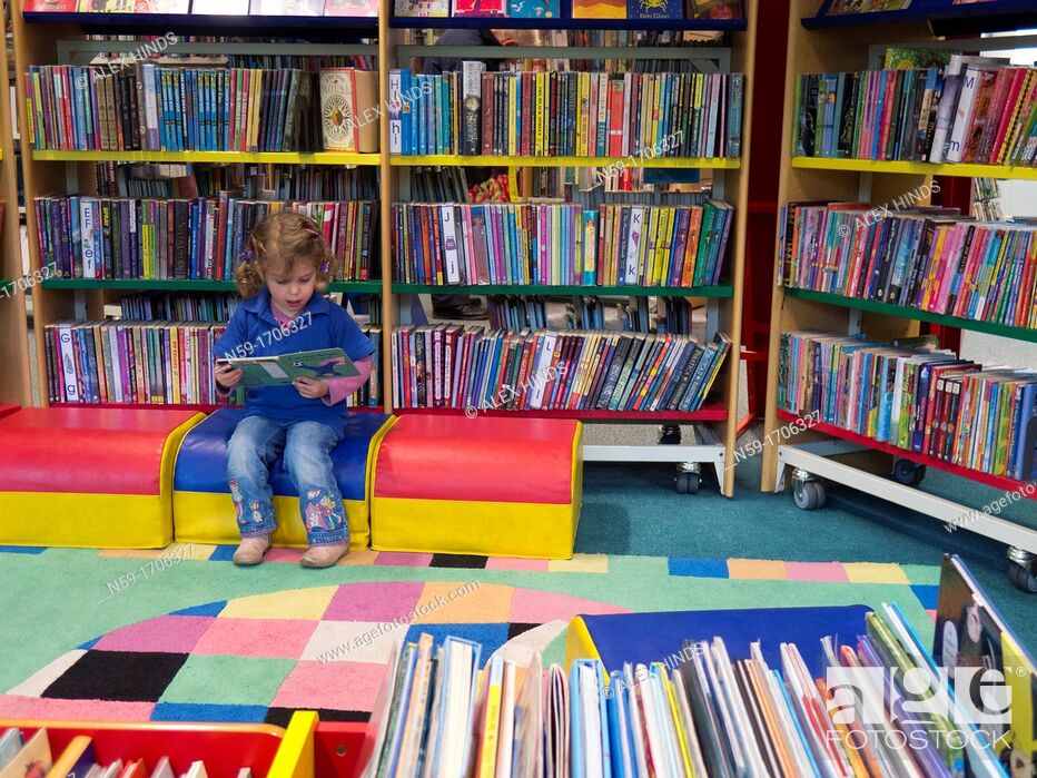 Stock Photo: Three year old caucasian girl in preschool top looking at books in a public library.