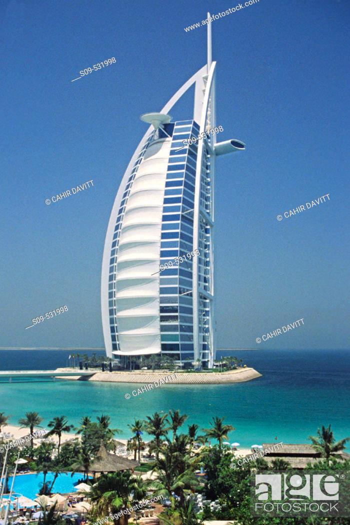 Stock Photo: The 7 star luxury Burj al Arab Hotel seen from the grounds of the 5 Star luxury Jumeirah Beach Resort Hotel at Jumeirah Beach, Dubai, United Arab Emirates.