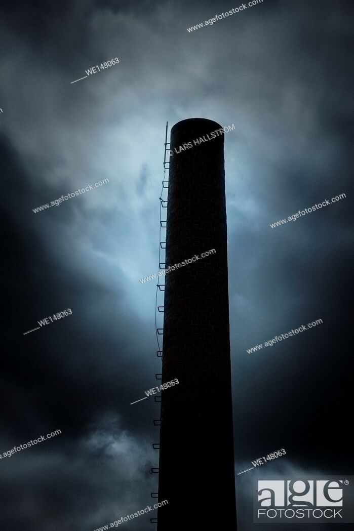 Photo de stock: Dark and ominous sky and silhouette of factory chimney. Heavy clouds and darkness. Moody and scary setting in industrial area.