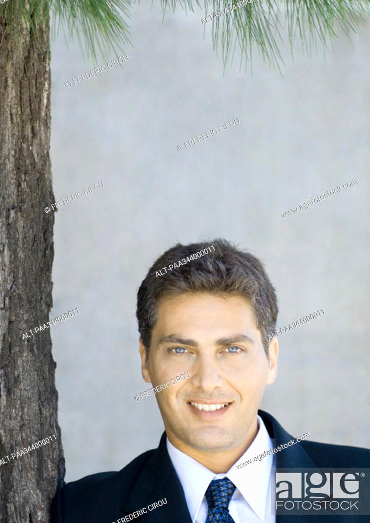 Stock Photo: Businessman next to tree, portrait.