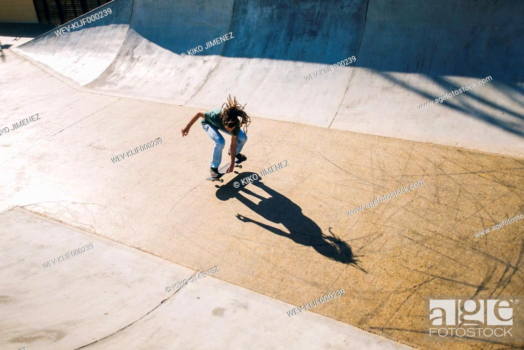 Stock Photo: Young man with dreadlocks skateboarding in a skatepark.