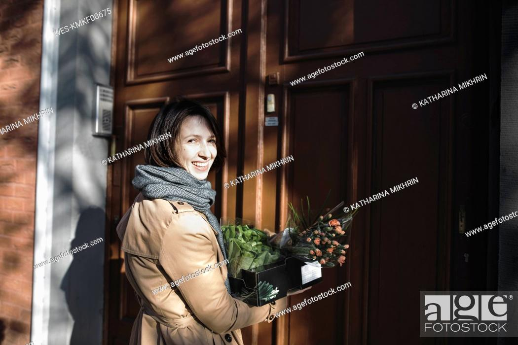 Photo de stock: Portrait of laughing woman with cardboard box of purchases standing in front of house entrance.