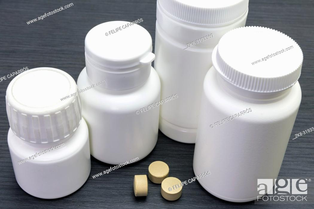 Stock Photo: white bottles of pills of different sizes, conceptual image.