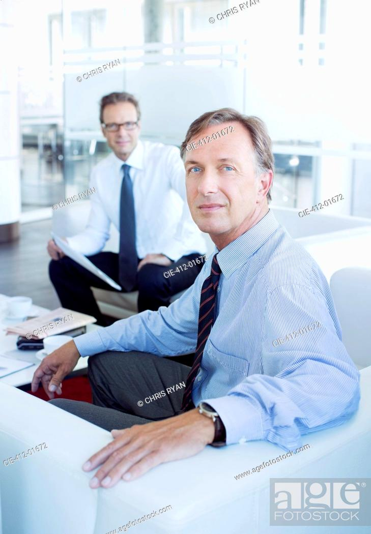 Stock Photo: Businessmen sitting in office lobby area.