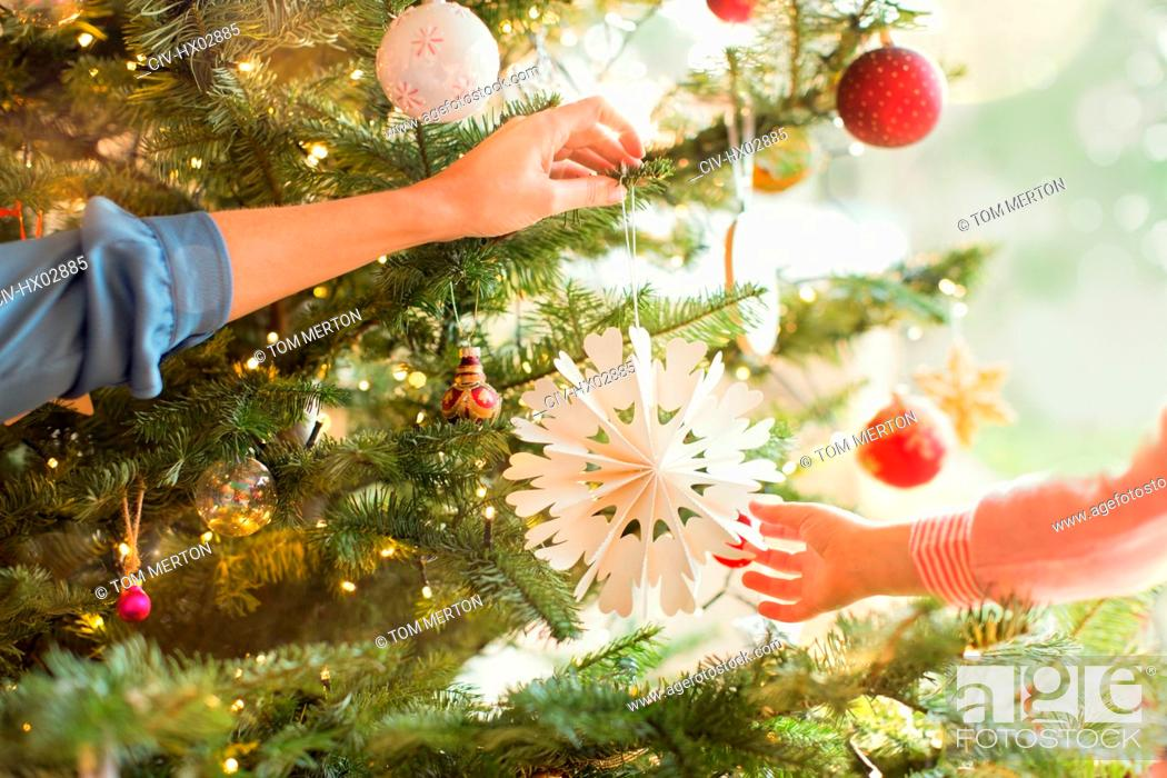 Stock Photo: Mother and daughter hanging snowflake ornament on Christmas tree.