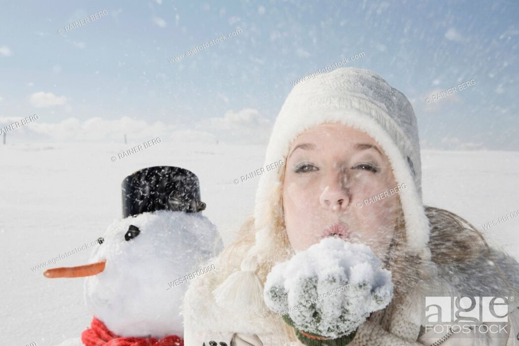 Stock Photo: Germany, Bavaria, Munich, Young woman blowing snow off hand, portrait.