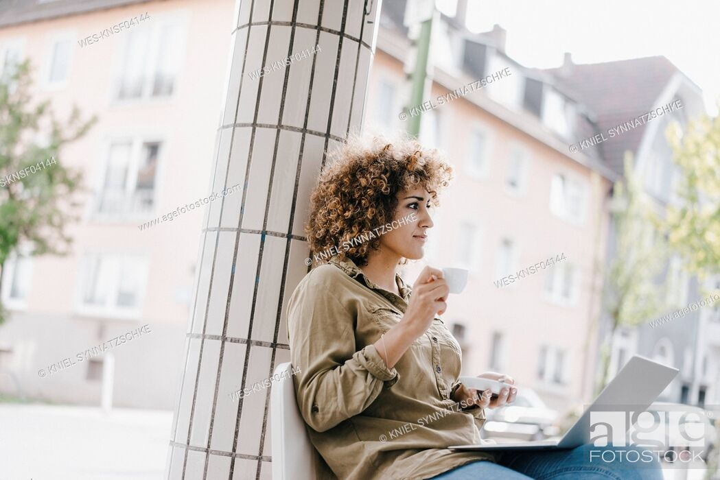 Stock Photo: Woman working in a cafe, drinking coffee, using laptop.