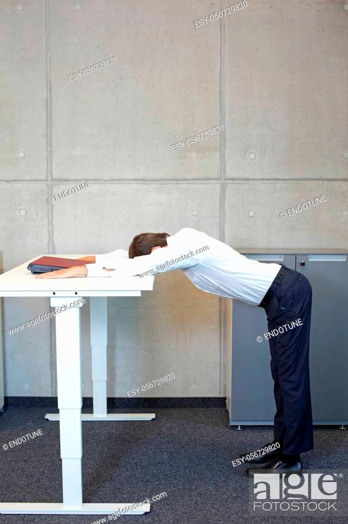 Stock Photo: yoga in office. business man exercising at electric height adjustable desk in office - stretching at desk.