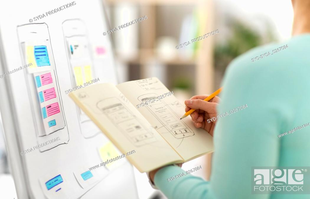 Stock Photo: ui designer with user interface sketch in notebook.