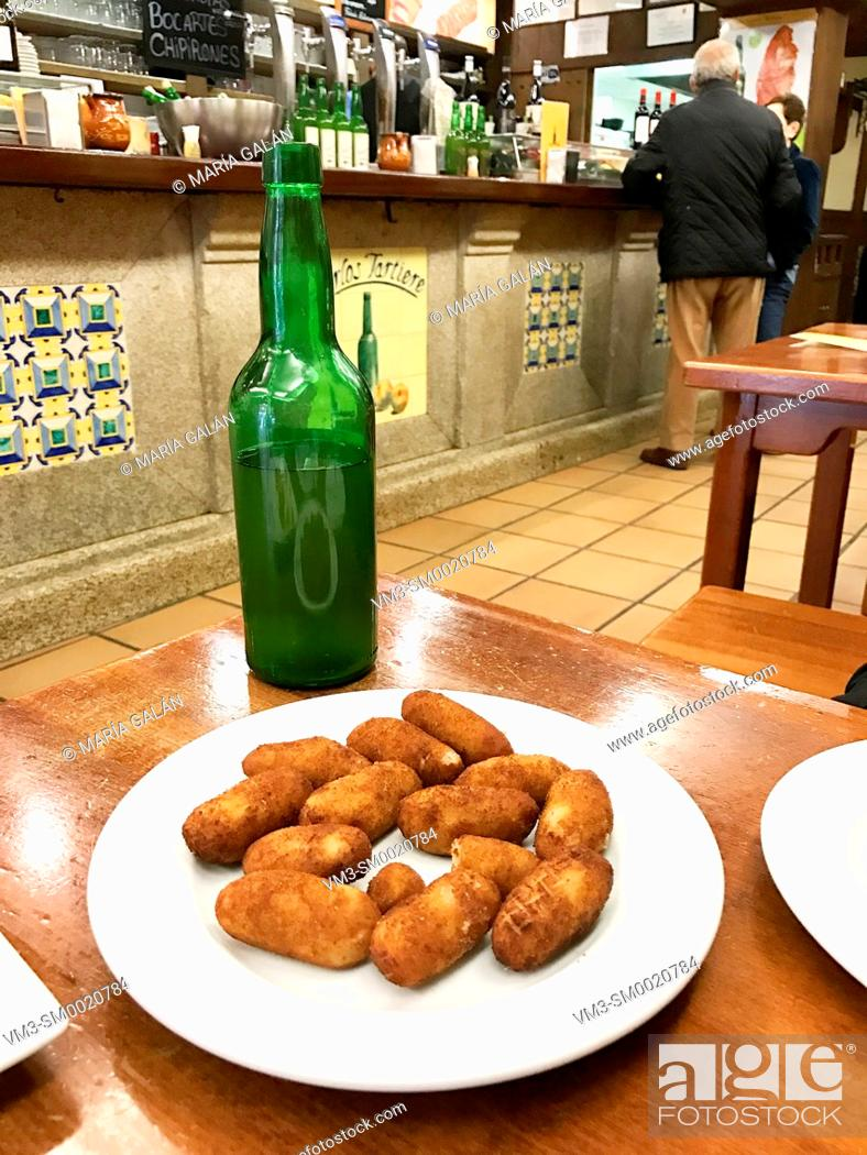 Stock Photo: Croquettes serving with bottle of cider in a restaurant. Madrid, Spain.