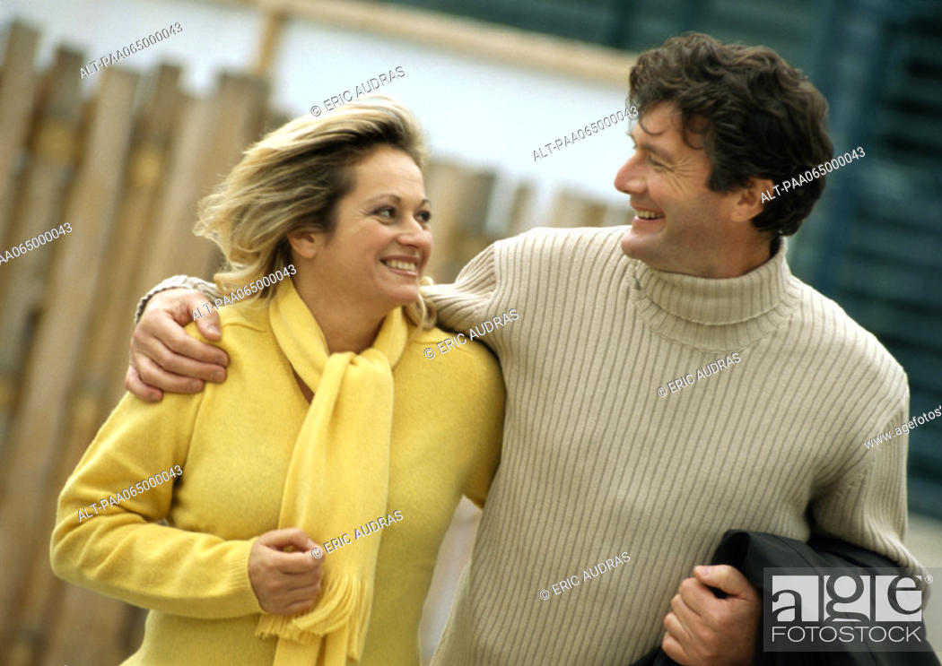 Stock Photo: Man and woman smiling at each other, man's arm around woman, waist up.