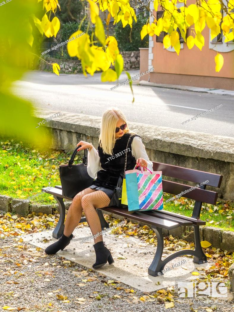 Stock Photo: Attractive mature blonde woman is holding shopping bags with both hands.