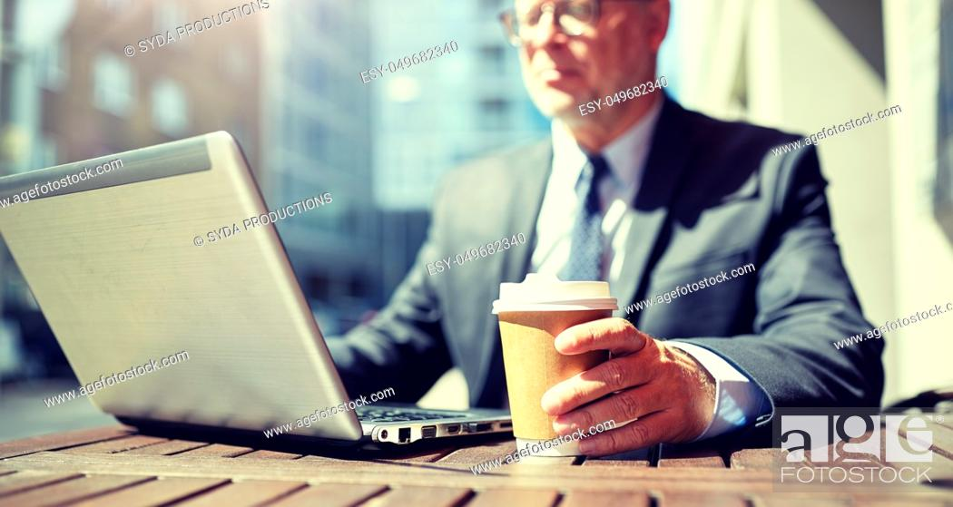 Stock Photo: senior businessman with laptop and coffee outdoors.