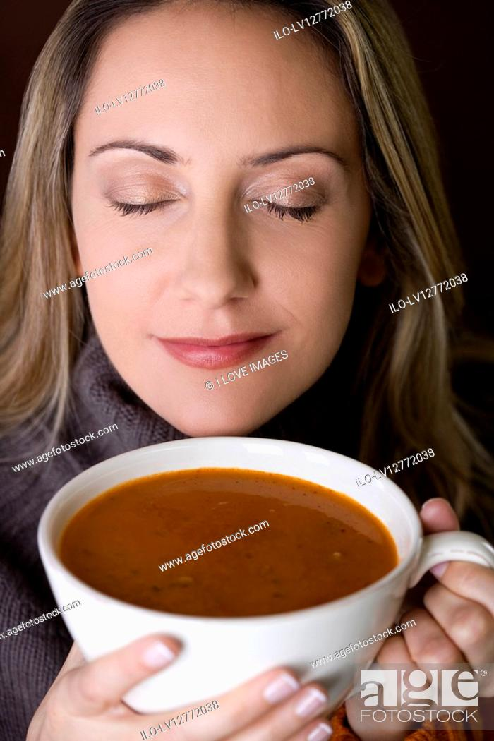 Stock Photo: A mid adult woman holding a cup of soup.