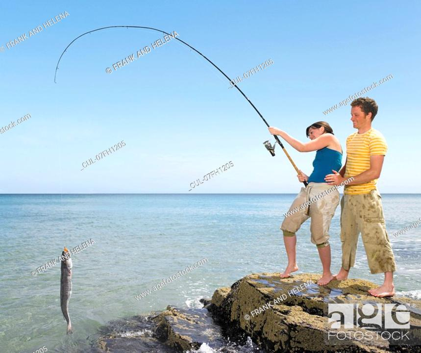Stock Photo: Couple landing a big fish off rocks.
