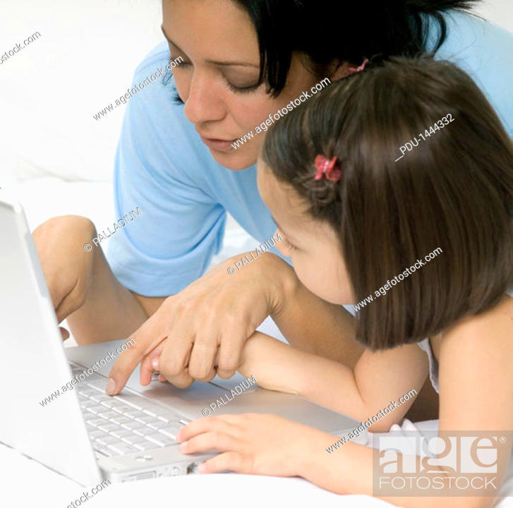 Stock Photo: Woman and girl using laptop computer on bed, close-up.