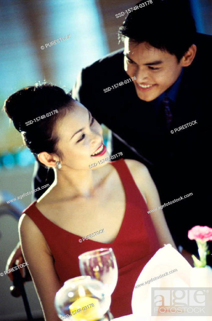 Stock Photo: Young couple smiling at each other at a dining table.