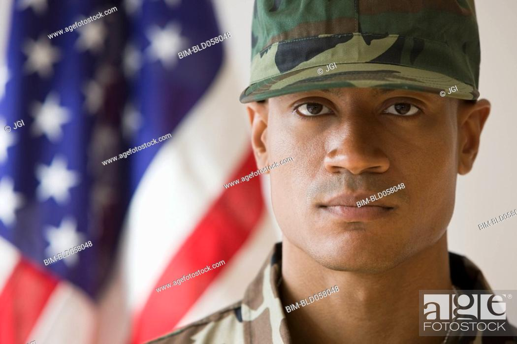 Stock Photo: African male soldier in front of American flag.