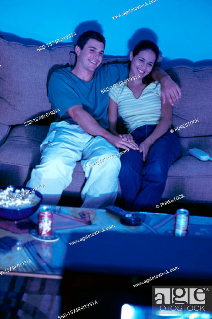 Stock Photo: Young couple sitting on a couch and watching television.