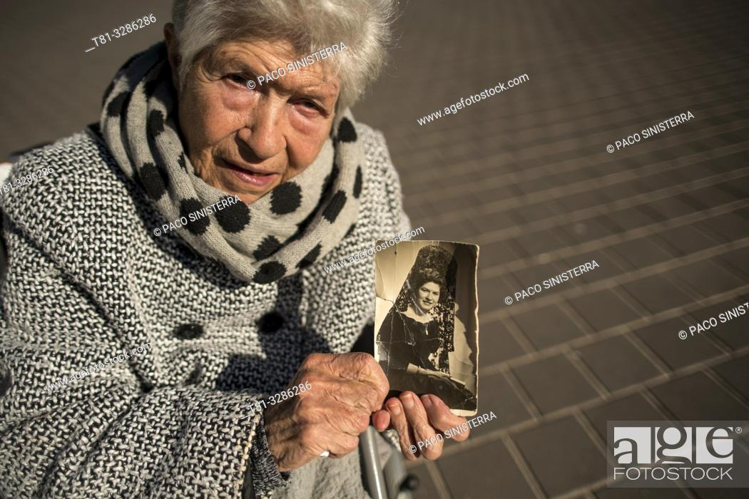 Stock Photo: Old woman holding a photo of her youth, memories.
