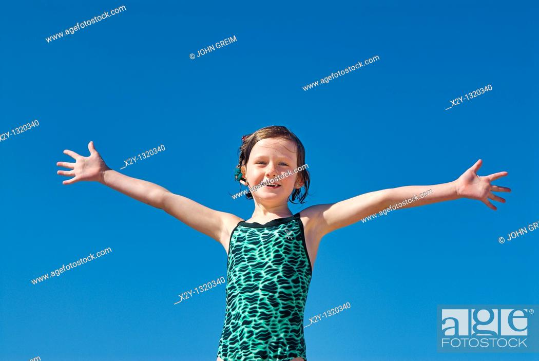 Stock Photo: Joyous girl in bathing suit and open arms at the beach.