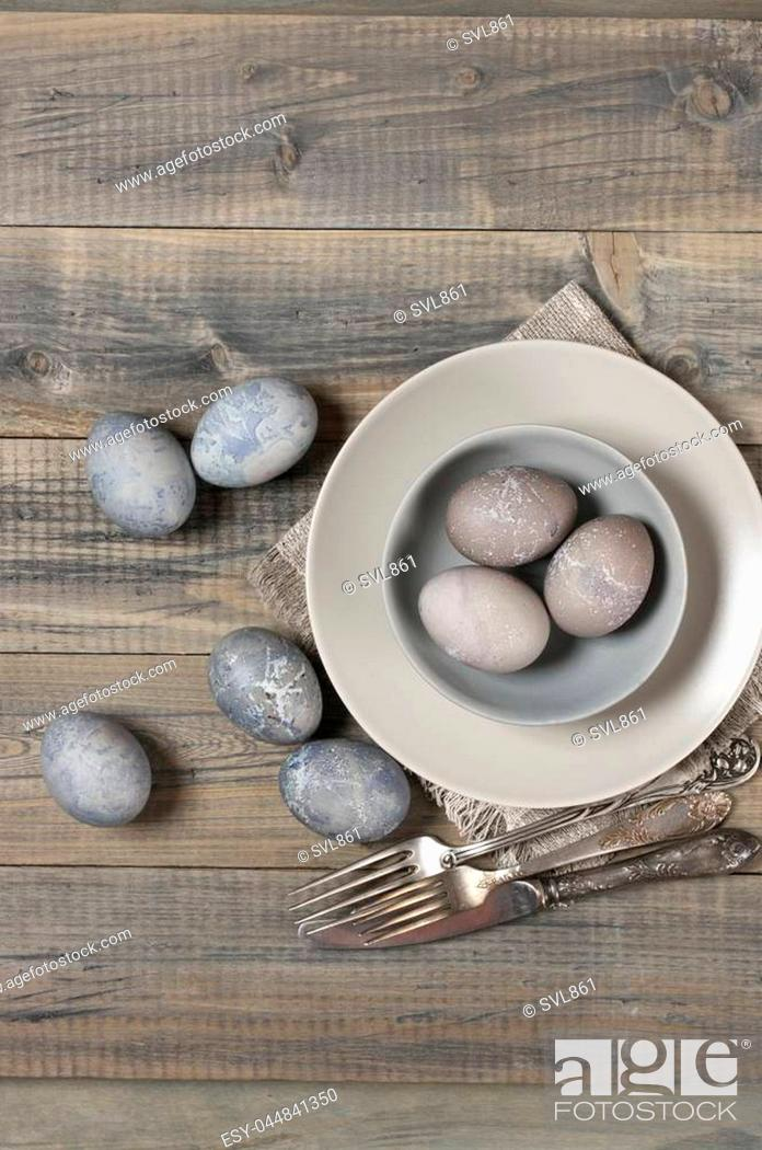 Stock Photo: Natural dyed grey Easter eggs in bowl and silverware on rustic grey wooden background. Top view point.