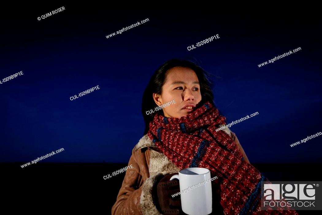 Stock Photo: Young woman wrapped in scarf on beach at night, Tarragona, Catalonia, Spain.