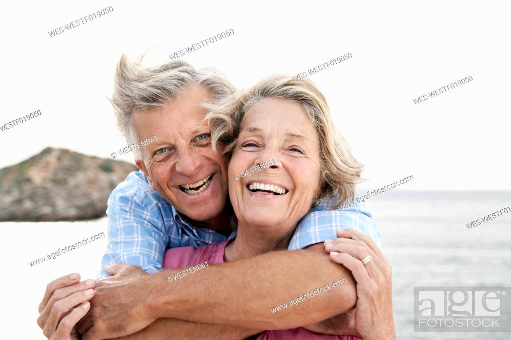 Stock Photo: Spain, Senior couple embracing at harbour, smiling.