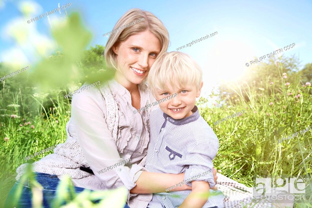 Stock Photo: Germany, Cologne, Mother and son sitting on blanket at picnic.
