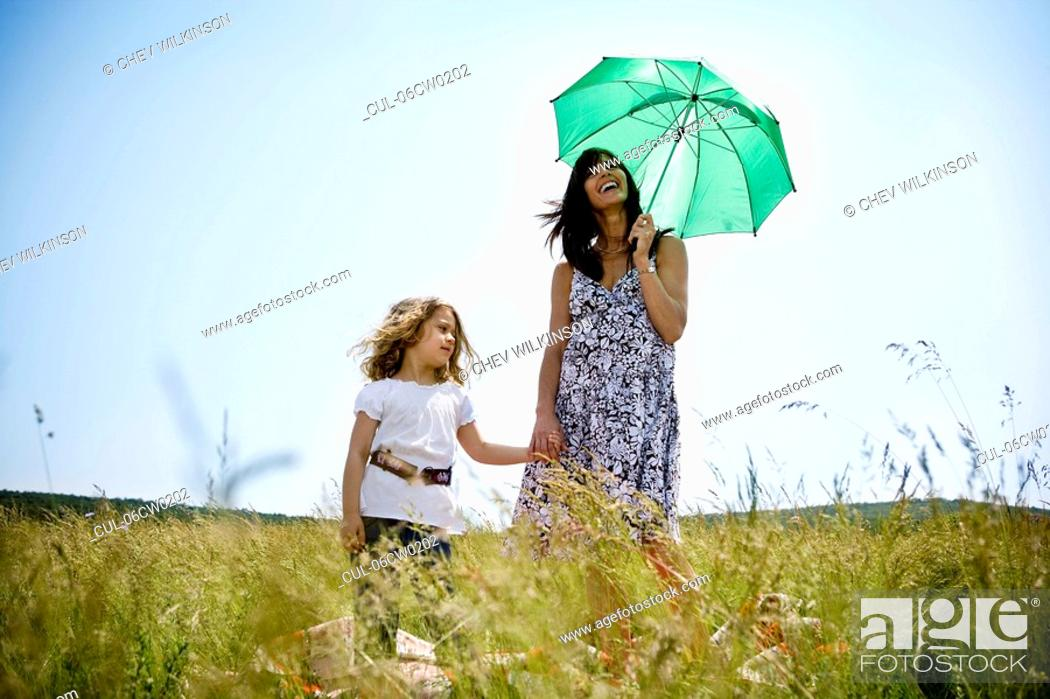 Stock Photo: Woman with daughter holding umbrella.