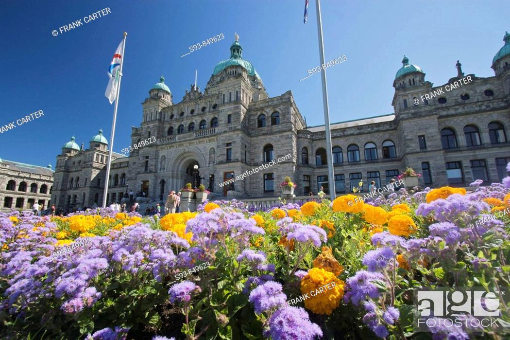 Stock Photo: A ground level view of the British Columbia parliament buildings, with yellow and purple flowers in the fore ground in Victoria city.